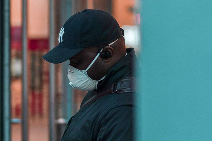 Black man wearing respirator mask outside