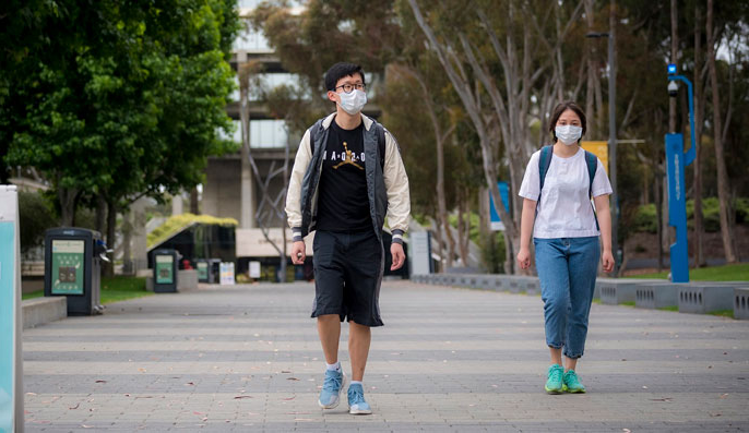 Two students walk with facemasks on